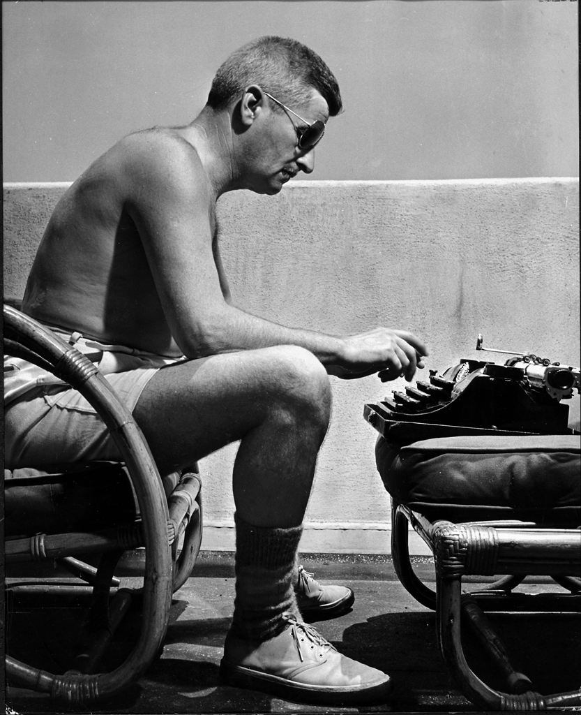 American author William Faulkner (1897 - 1962) works on a screenplay at his typewriter on a balcony, Hollywood, California, early 1940's. He is shirtless and wears shorts, heavy wool socks, shoes and sunglasses. (Photo by Alfred Eriss/Pix Inc./Time Life Pictures/Getty Images)